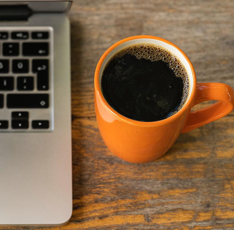 orange mug filled with coffee next to a laptop